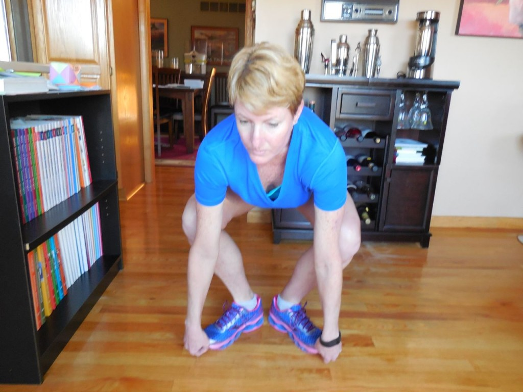 go down into a squat while holding on to your toes